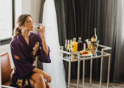 Bride drinking champagne in suite